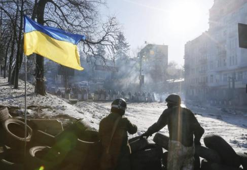 Dos manifestantes en una barricada delante de un cordón policial en...