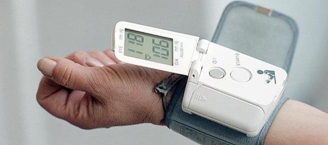 Un hombre se mide la tensión arterial con un dispositivo para la...