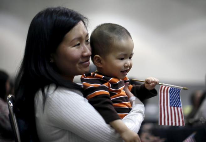 Inmigrantes vietnamitas con una bandera estadounidense durante una...