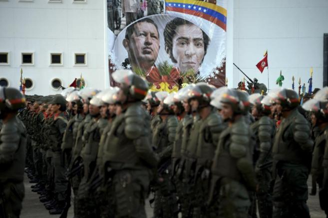 Militares venezolanos hacen guardia frente a un poster de Chávez y...