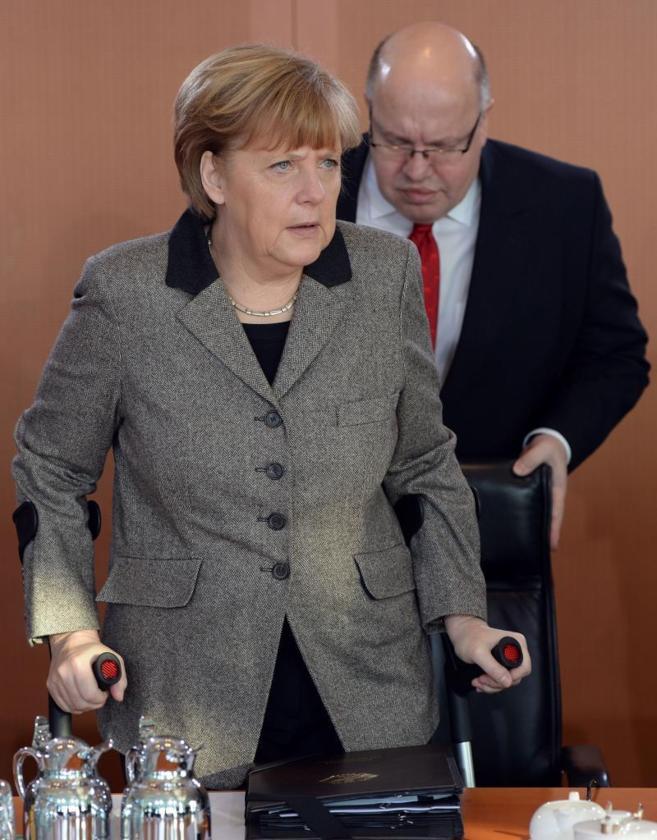 Peter Altmaier, jefe de personal de Merkel, ayuda a sentarse a la...