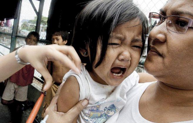 Una niña lora mientras le ponen una vacuna