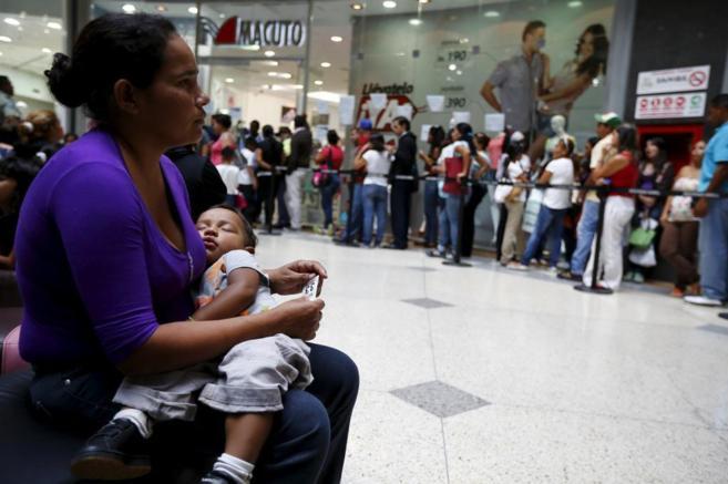 Una mujer con un bebé hace turno en una cola en Caracas para comprar.