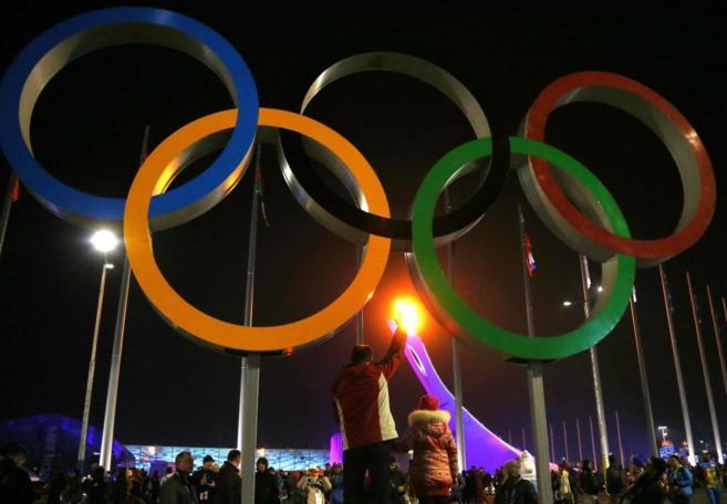 Imagen de los aros olímpicos con la llama olímpica de fondo.