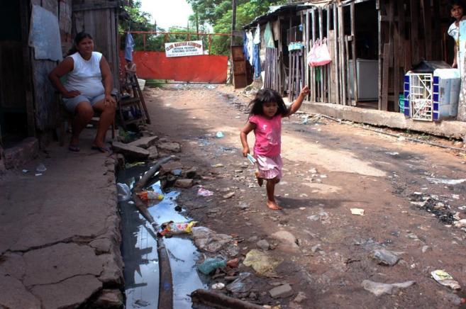 Una niña juega en un barrio de chabolas de Paraguay