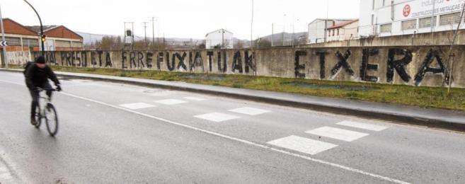 Un ciclista pasa ante una gran pintada en Vitoria que pide el regreso...