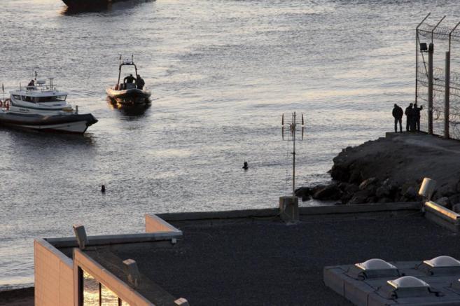 Miembros de la Guardia Civil vigilan por mar y tierra en el perímetro...