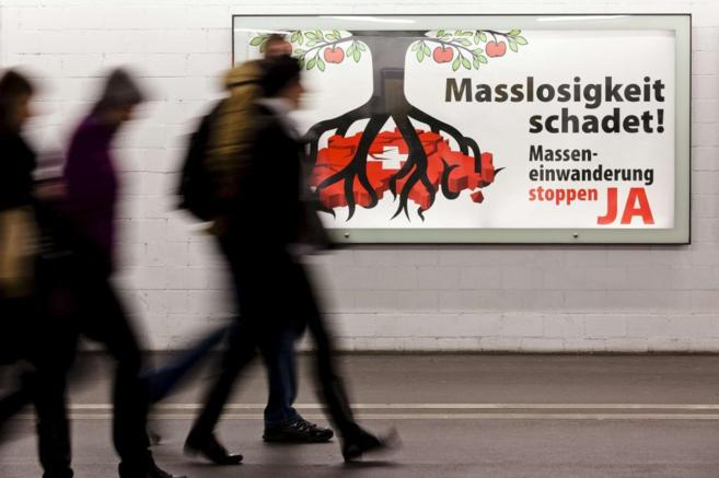 Varias personas pasan, en Zurich, junto a un cartel que reza...