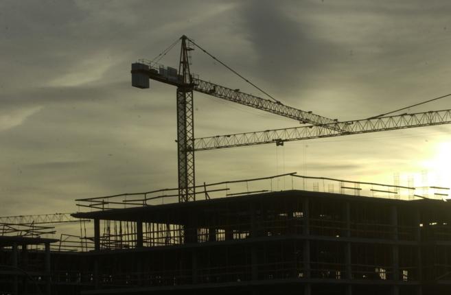 Varias grúas en la construcción de un edificio de viviendas en...
