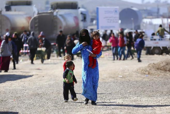 Una mujer siria camina con sus hijos en el campo de refugiados de Quru...