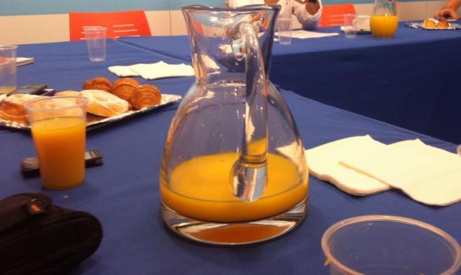 Zumo de naranja y bollos sobre una mesa.