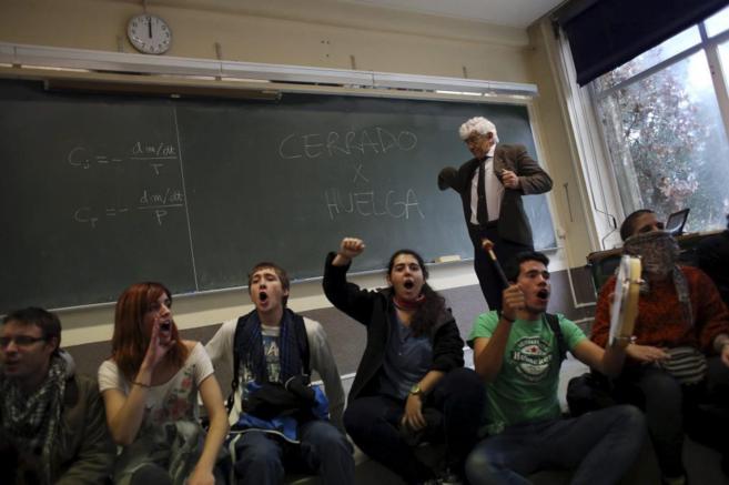 Estudiantes están sentados en el suelo, gritan y hacen música, en el...