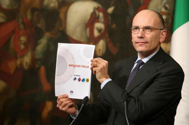El primer ministro, Enrico Letta muestra el documento '...