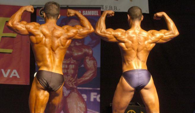 Dos culturistas, de espaldas,durante una exhibición.