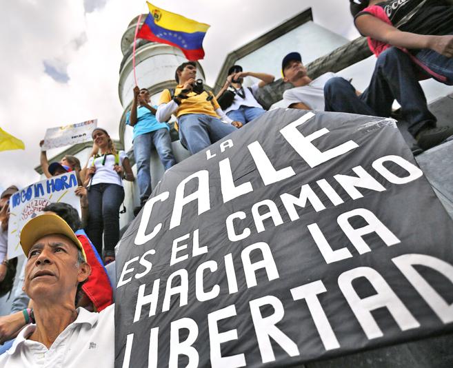 Un opositor venezolano sujeta un cartel reclamando libertad durante la...
