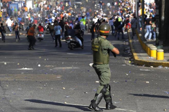 Un miembro de la Guardia Nacional apunta a los manifestantes en...