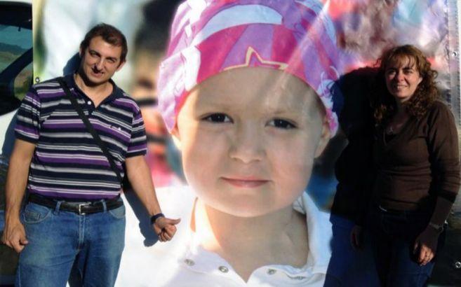 Un hombre y una mujer delante de una foto gigante de una niña con...