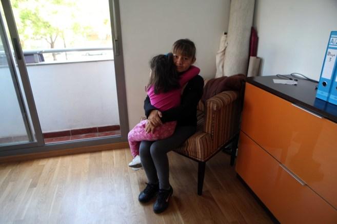 Una mujer abraza a una niña en una de las viviendas ocupadas de la...