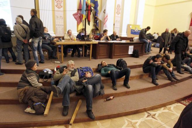 Varios manifestantes ucraniano descansan en el Ayuntamiento de Kiev.