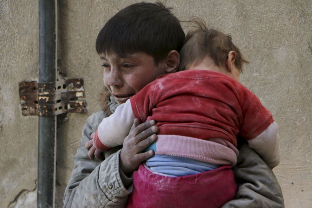 Un niño sirio lleva a su hermana pequeña en brazos para huir de los...