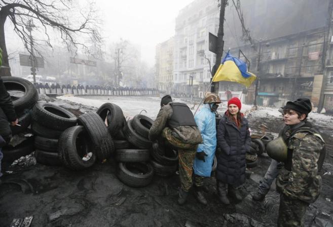 Manifestantes ucranianos reunidos junto a una barricada en Kiev.