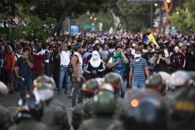 Jóvenes encapuchados participan en las protestas.