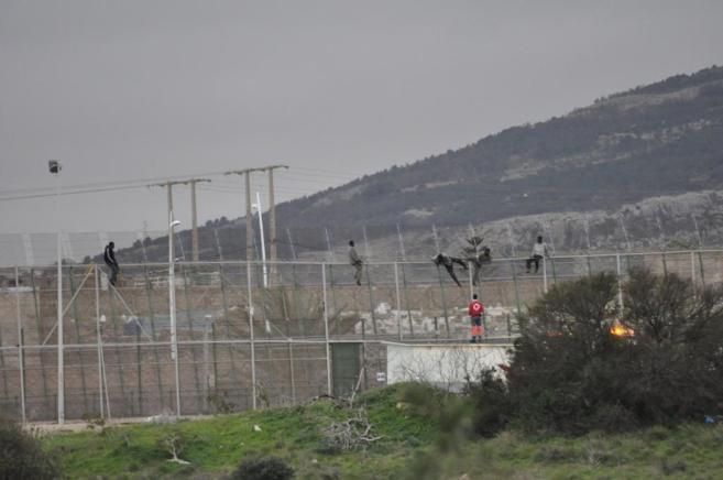 Algunos de los inmigrantes que entraron en Melilla, saltan la valla en...