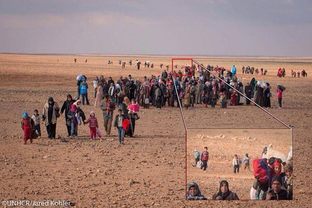 Detalle de la llegada de Marwan a la frontera siria con Jordania. En la imagen, colgada en Twitter por  Andrew Harper, responsable de ACNUR en Jordania, se puede ver como llega solo, con tan solo una bolsa en su mano y rodeado de niños. Harper explica que Marwan aparece separado del grupo de refugiados, pero que él no estaba solo.