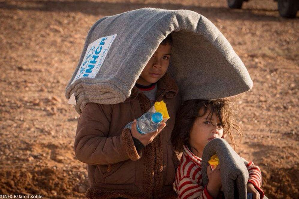 Dos de los miles de niños que se encuentran en el campamento de refugiados. En la imagen se les puede ver con una botella de agua, un paquete de galletas y unas mantas a su llegada el pasado 23 de enero. Como Marwan huyen de la guerra.