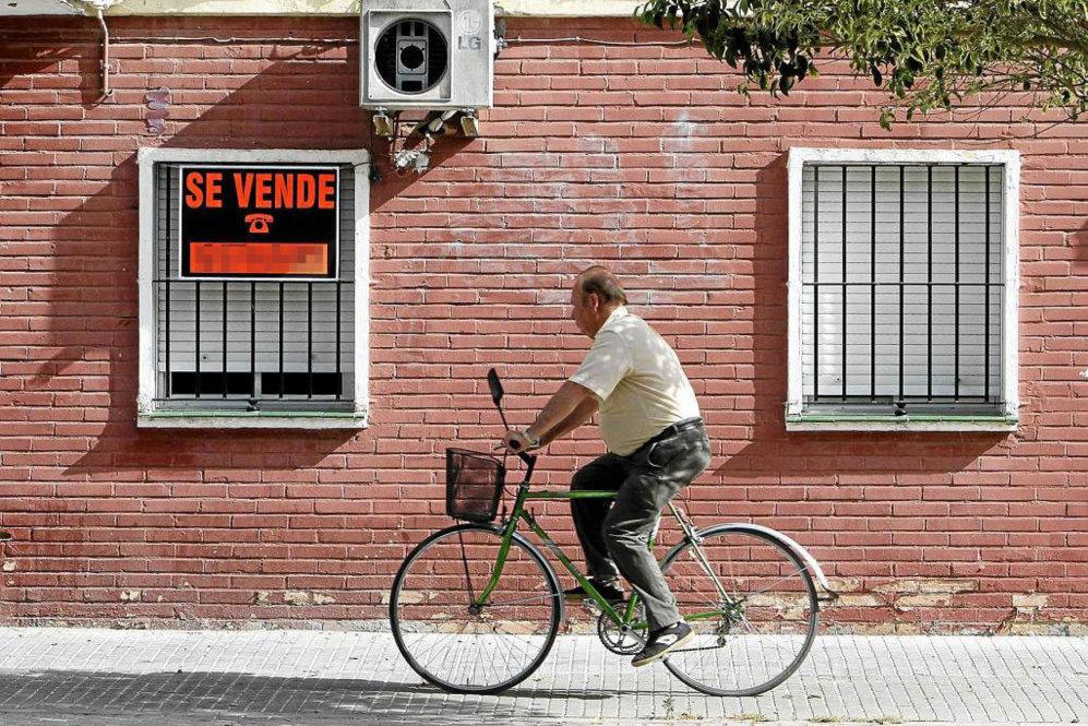 Un hombre en bicicleta pasa por delante de una vivienda con un cartel...