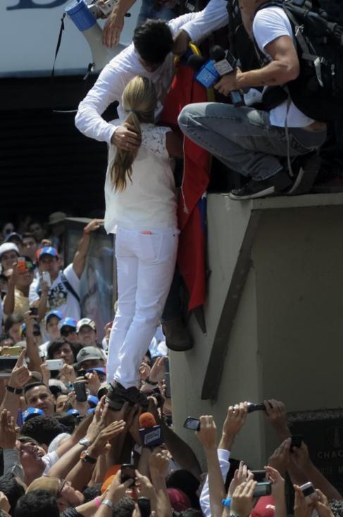 Leopoldo López se despide de su esposa, izada por sus partidarios.