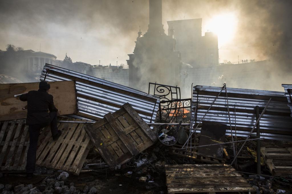 Un hombre escala una barricada hoy, en Kiev.