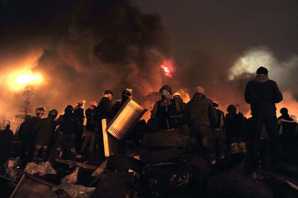 Varios manifestantes montan guardia entre barricadas ardiendo, esta...