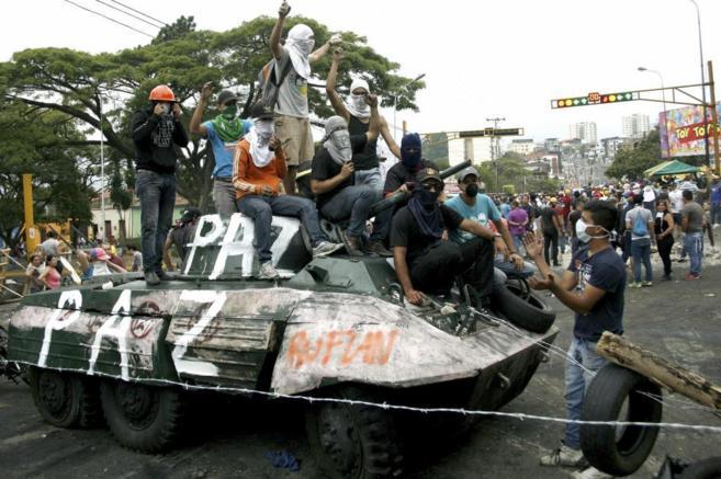 Un grupo de opositores en un tanque usado a modo de barricada en San...