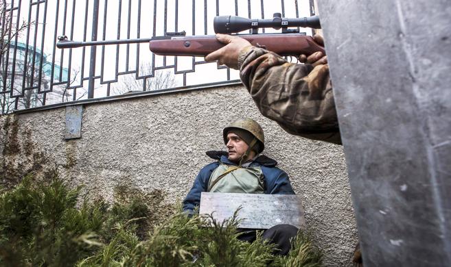 Un manifestante apunta el arma en dirección a un francotirador cerca...