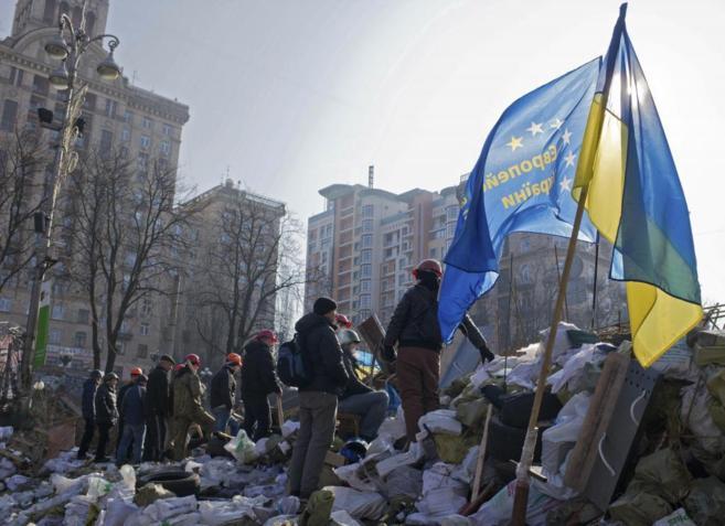 Manifestantes en pie en una barricada en una calle de acceso a la...