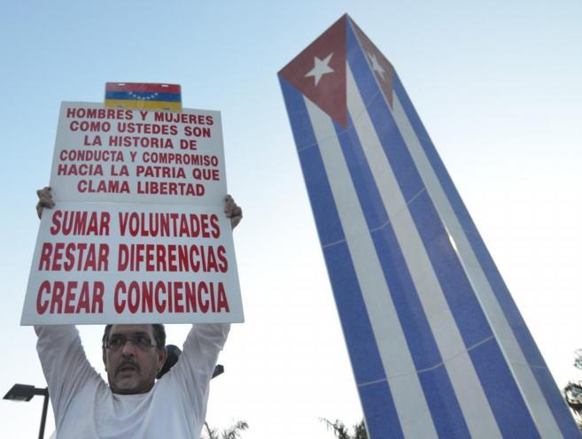 Un hombre levanta un cartel frente al Memorial Cubano levantado en...