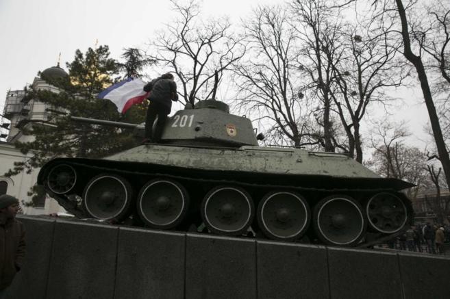 Un ruso-ucraniano coloca una bandera de Crimea en un viejo carro de...