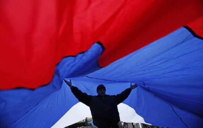 Un hombre lleva una bandera rusa gigante durante una manifestación en...