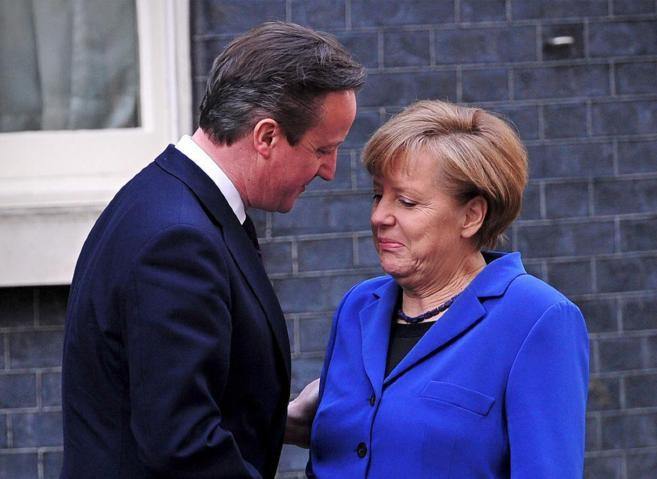 El primer ministro británico, David Cameron, saluda a la canciller...