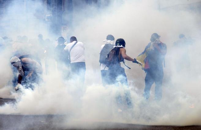 Manifestantes venezolanos se enfrentan a la policía en las calles de...
