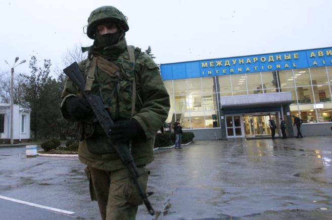 Un hombre armado patrulla en los alrededores del aeropuerto civil en...
