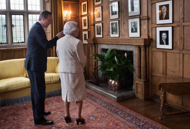Isabel II mira las fotos que le muestra el primer ministro Cameron en...