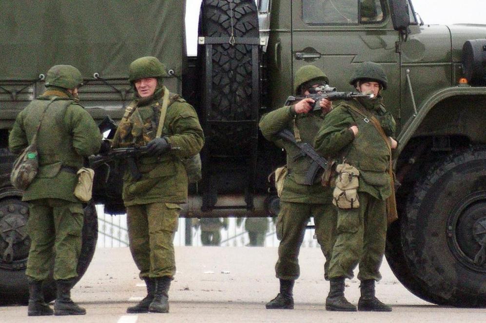 Un grupo de soldados sin identificar montan guardia en una carretera...