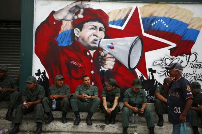 Soldados venezolanos bajo un mural del fallecido Hugo Chávez, en...
