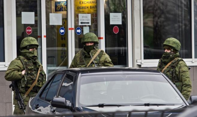 Un grupo de hombres armados patrulla a la entrada del aeropuerto de...