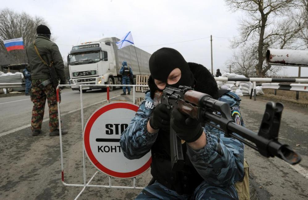 Un hombre armado apunta con un Klashnikov, en un punto de control, en...