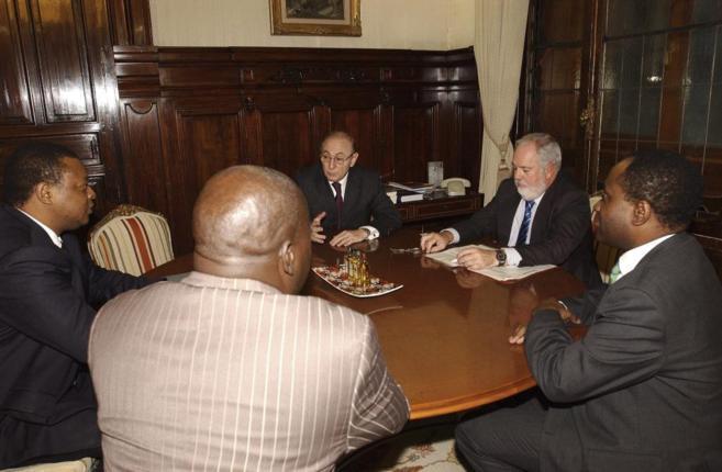 El ex embajador (de frente, izquierda), con el ministro de...