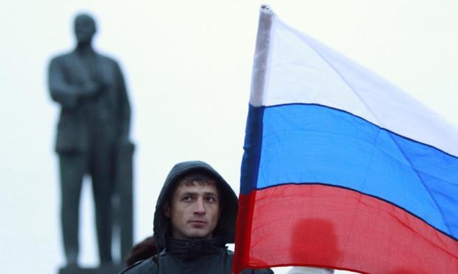 Un hombre con la bandera rusa, frente a una estatua de Lenin, en...