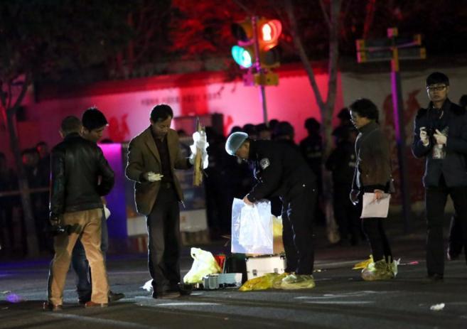 Agentes de policía examinan objetos después del ataque.